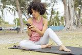 Chilling black girl using phone on mat