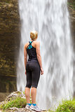 Active woman looking at Pericnik waterfall in Vrata Valley in Triglav National Park in Julian Alps, Slovenia.