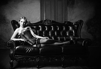 Sensual young girl dressed in corset, stockings and panties lying on sofa. Black and white portrait. Retro (vintage) style