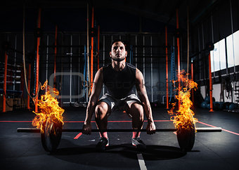 Athletic man works out at the gym with a fiery barbell