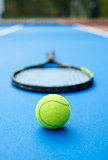 Yellow ball on tennis racket background.