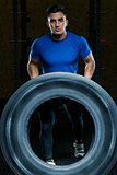 portrait of a strong athlete with a large heavy wheel in the gym