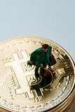 miniature man on a pile of bitcoins