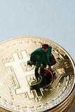 miniature man on a pile of bitcoins
