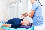 Physio treating senior patient