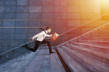 Businessman runs fast over a modern staircase