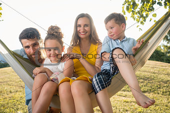 Family portrait with beautiful mother of two children next to her husband