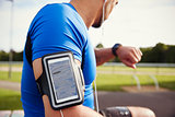 Male athlete wearing smartphone armband checking smartwatch
