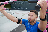Young male athlete using outdoor gym in park, close up