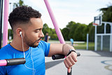 Young man at outdoor gym checking fitness app on smartwatch