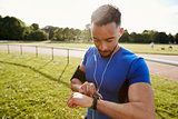 Young man at running track setting fitness app on smartwatch