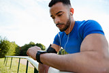 Male athlete at track checking smartwatch app, close up