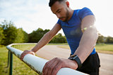 Male athlete leaning on fence at running track, close up