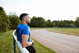 Male athlete wearing earphones taking a break at a track