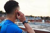 Male runner adjusting earphones in urban setting, close up