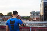 Male runner adjusting earphones in urban setting, back view