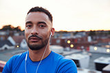 Male runner in urban setting looking to camera, close up