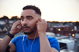Male runner in urban setting adjusting earphones, close up