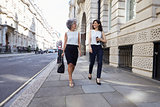 Two female colleagues walking in the street talking