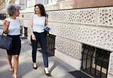 Two female work colleagues walking in the street talking