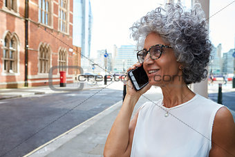 Middle aged woman talking on phone in city street, close up