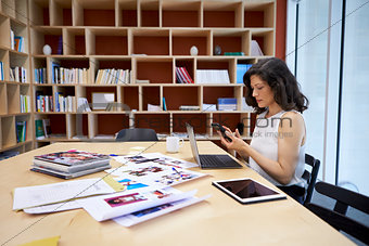 Woman in creative media office using smartphone at her desk