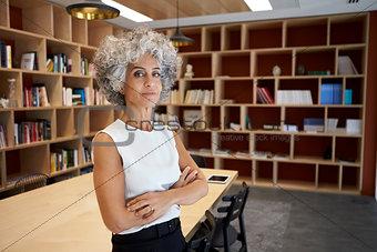Senior businesswoman standing in boardroom looking to camera