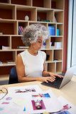 Senior businesswoman working on laptop in office, vertical