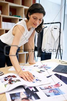 Female media creative working on magazine layout, vertical