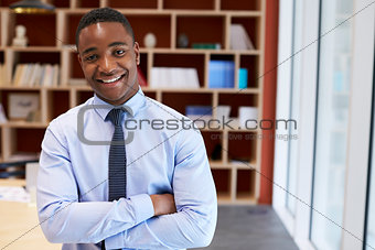 Young black businessman smiling to camera in a boardroom