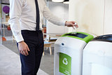 Man in an office throwing plastic bottle into recycling bin