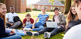 Teenage Students Sitting Outdoors And Working On Project