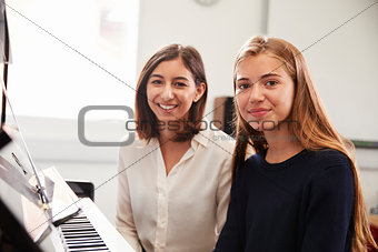 Portrait Of Pupil With Teacher Playing Piano In Music Lesson