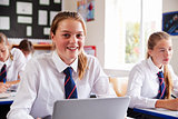 Portrait Of Female Pupil In Uniform Using Laptop In Classroom