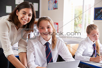 Portrait Of Teacher Helping Pupil Using Computer In Classroom