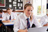 Female Pupil Wearing Uniform Using Laptop In Classroom
