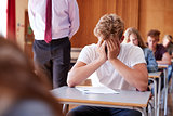 Anxious Teenage Student Sitting Examination In School Hall