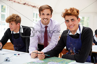 Portrait Of Male Teacher Helping Teenage Pupils In Art Class