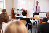 Teenage Students Listening To Male Teacher In Classroom