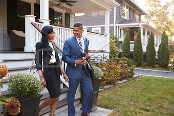 Business Couple Leaving Suburban House For Commute To Work