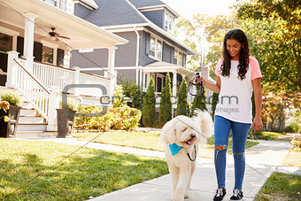 Girl Walking Dog Along Suburban Street