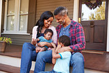 Family With Baby Son Sit On Steps Leading Up To Porch Of Home