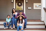 Family With Children Sit On Steps Leading Up To Porch Of Home