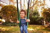 Happy Young Girl Playing On Garden Swing