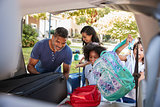 Family Leaving For Vacation Loading Luggage Into Car