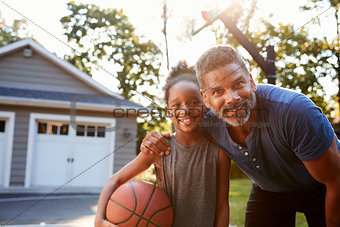 Portrait Of Father And Son Playing Basketball On Driveway