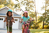 Sister With Brother Riding Scooter And Bike On Driveway At Home