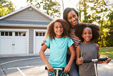 Mother With Children Riding Scooters On Driveway At Home