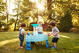 Group Of Young Children Playing With Water Table In Garden