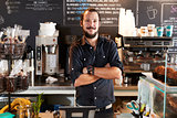 Portrait Of Male Barista Behind Counter In Coffee Shop